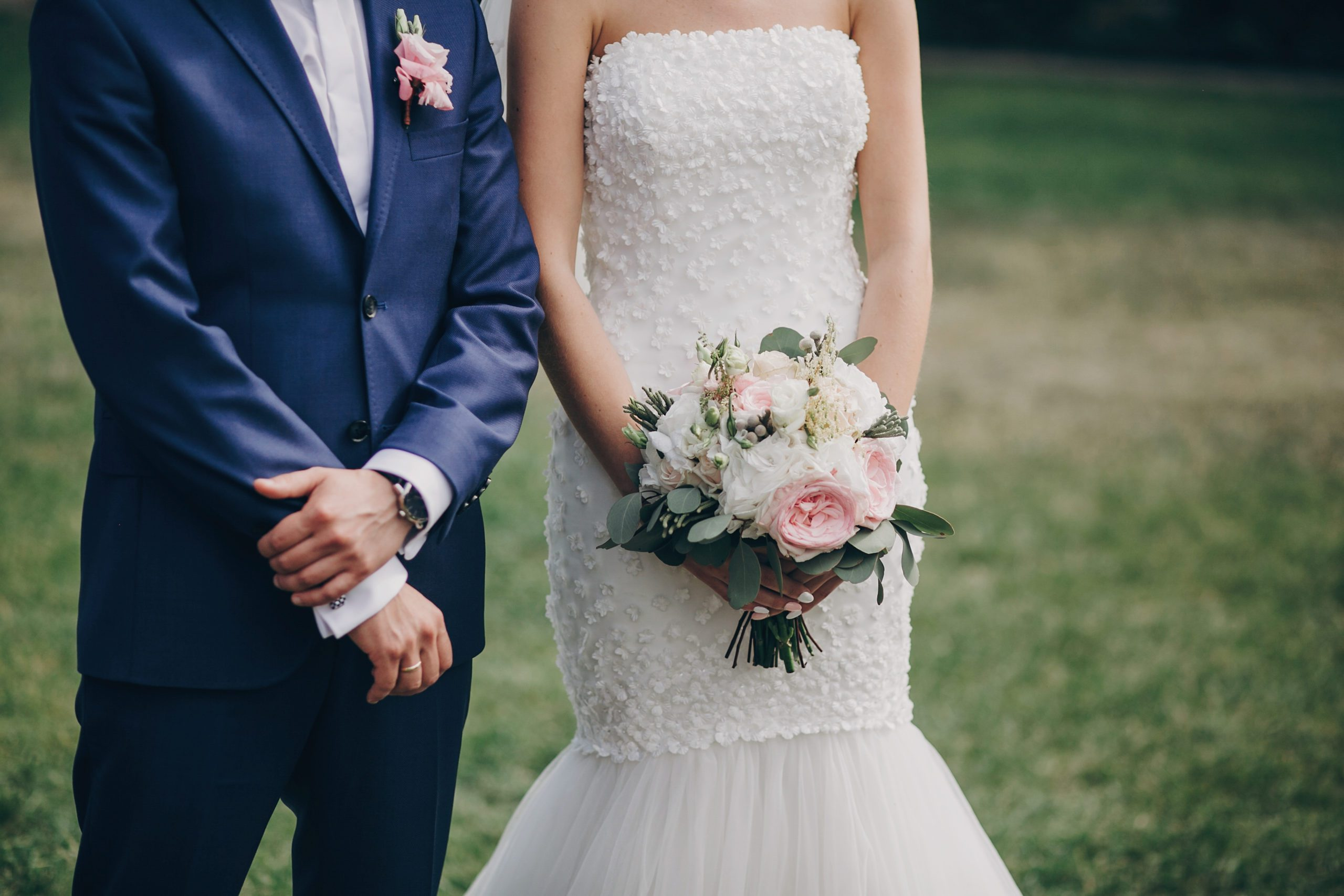 Stylish bride with bouquet and groom standing in wedding aisle with rose petals on grass during matrimony, cropped view . Beautiful wedding ceremony in summer park or garden