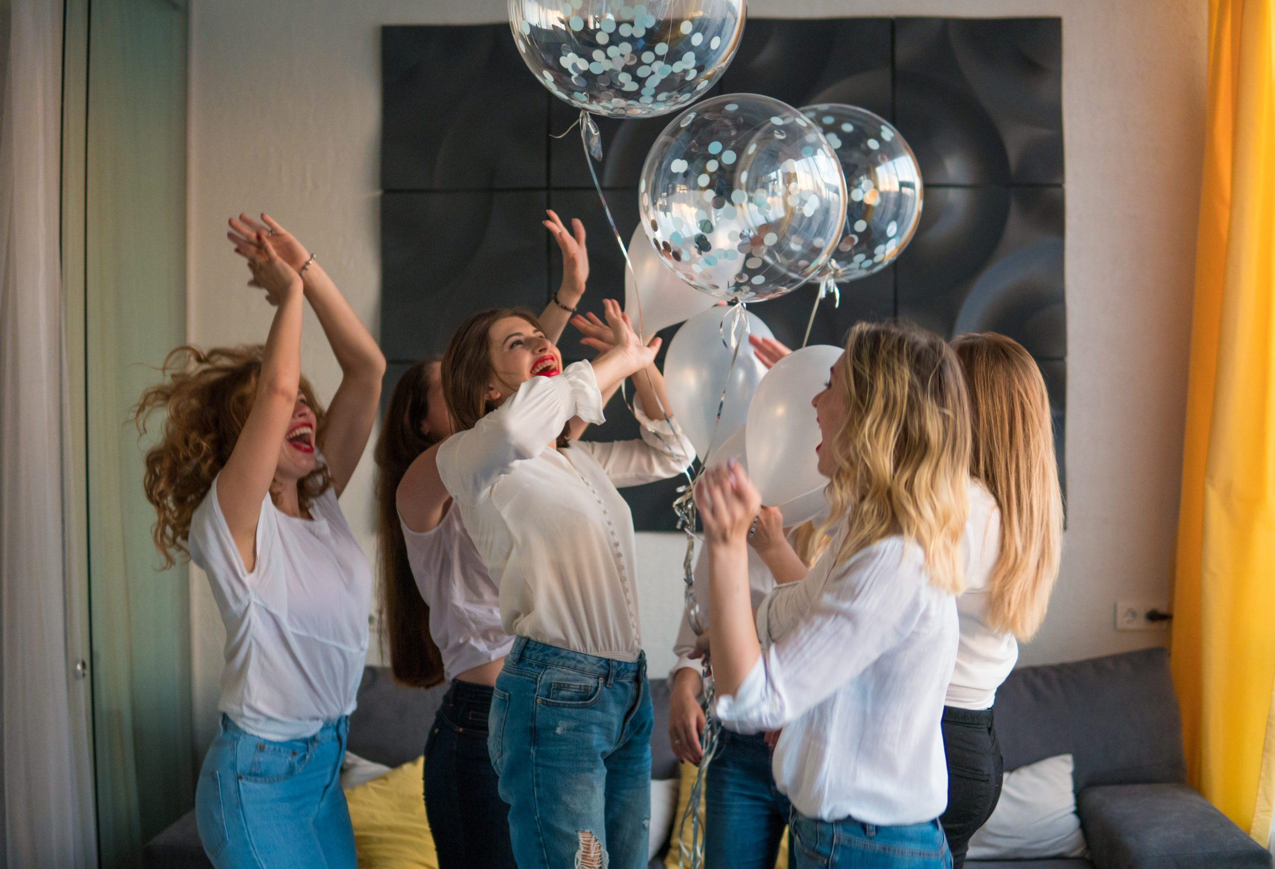 Girls Party. Beautiful Women Friends At Bachelorette Party. They dance with baloons.