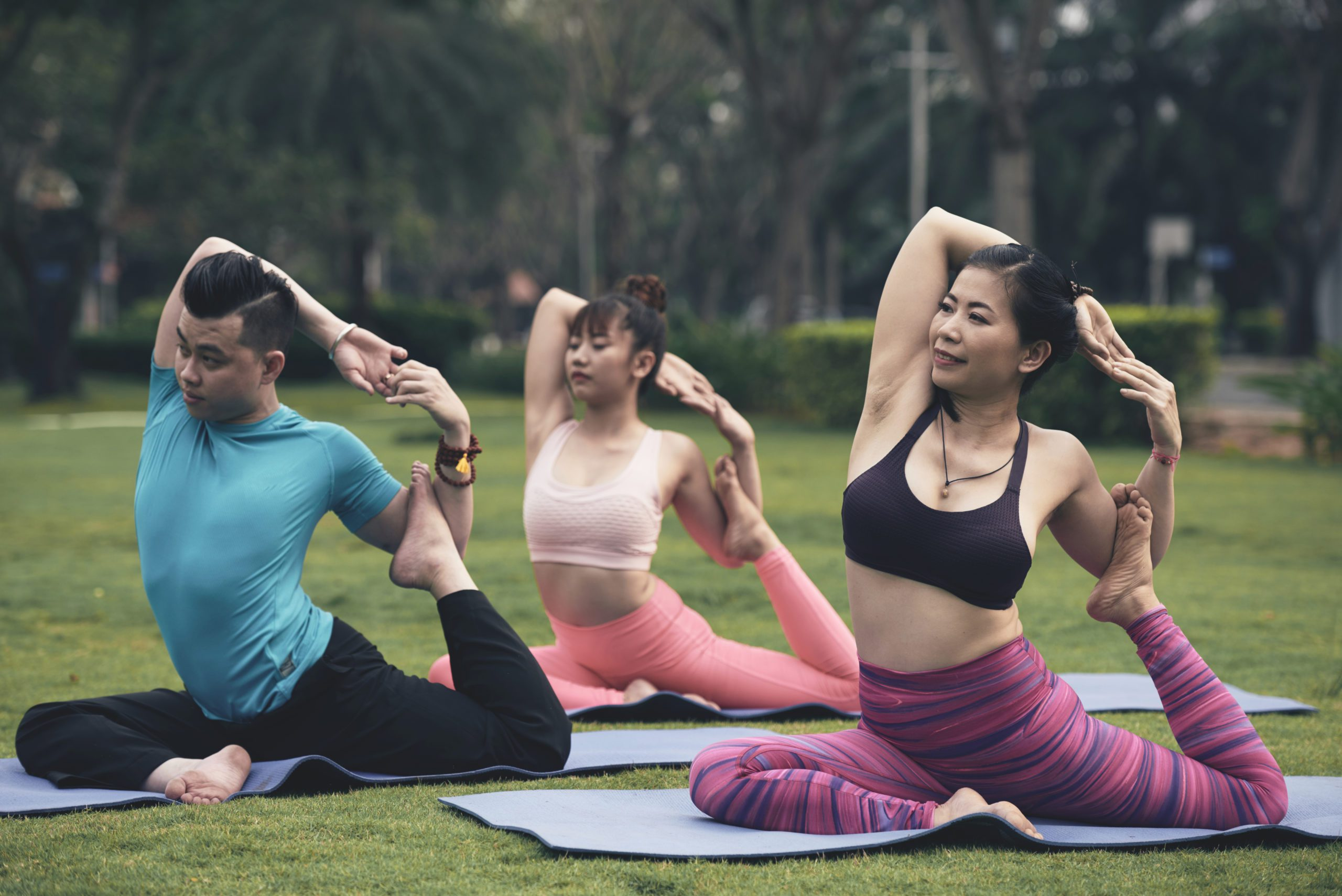 Young Asian people practicing pigeon yoga position outdoor