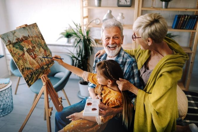 Happy smiling grandparents and grandchild painting together. Family, generation, happiness concept