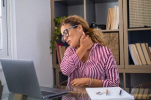 Office worker grabbing neck because of pinched nerves